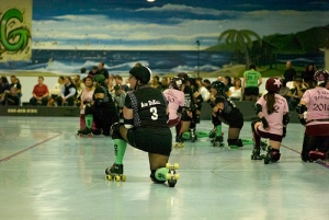 Skaters take a knee after Wrench Wench took a nasty spill. Later she was diagnosed with a spiral fracture of her tibia. Credit: nocklebeast.